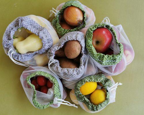 Zöldségek és gyümölcsök hálós bevásárló zsákokban